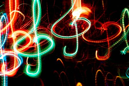 Close-up red and green neon glowing treble clefs. Abstract  luminous background.
