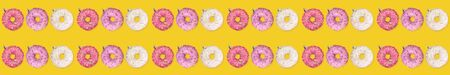 Wide festive creative christmas banner pattern of colorful donuts as Christmas tree toys on yellow background. Xmas decorations. Imagens