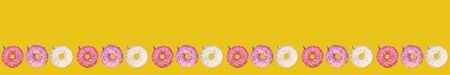 Wide festive creative christmas banner row of colorful donuts as Christmas tree toys on bright yellow background with copy space. Imagens