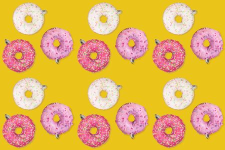Christmas decorations. Festive creative seamless pattern of of colorful donuts as Christmas tree toys on trendy yellow background. Horizontal orientation.