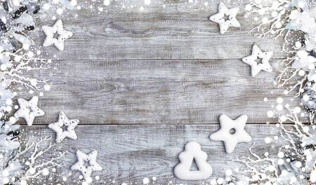 Christmas festive mockup in white. Xmas decorations. Creative frame of white Christmas toys stars, gingerbreads with white icing, snowy twigs, tinsel and snow on white wooden background. Top view, flat lay, copy space.