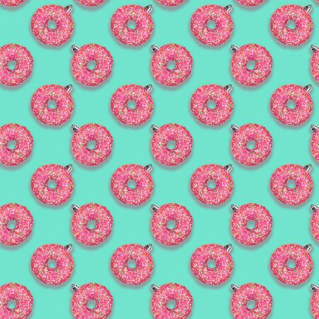 Christmas festive creative seamless pattern of bright pink donuts as Christmas tree toys on turquoise aquamarine background. Square photo. Christmas decorations.