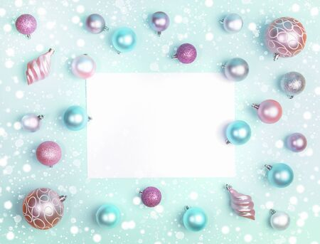 Xmas decorations mockup flat lay. Christmas festive frame of Christmas balls and snow with blank white sheet on trendy Neo Mint background. Top view, flat lay, copy space. Imagens