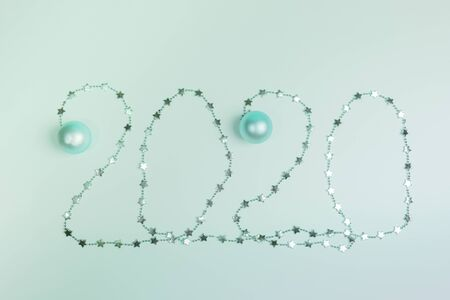 Christmas festive layout in trendy Neo Mint color. Creative numbers 2020 of shiny Christmas garland with small stars and Christmas balls. Top view, flat lay. Imagens