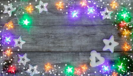 Christmas festive mockup. Xmas decorations. Creative frame of white Christmas toys stars, gingerbreads with white icing, multicolored garland with luminous stars and snow on white wooden background. Top view, flat lay, copy space.