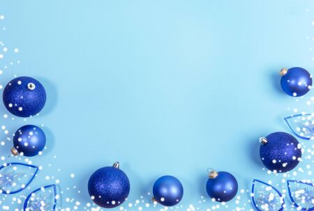 Christmas festive mockup. Xmas decorations. Bottom border of bright blue Christmas balls, lights-stars and snow on light blue background. Top view, flat lay, copy space.