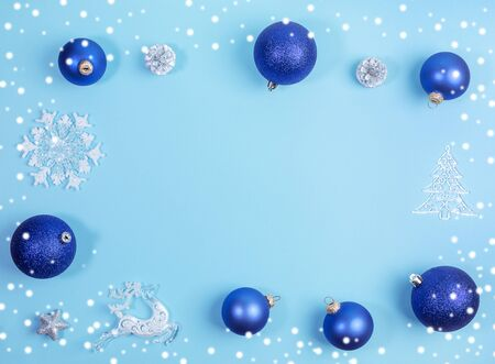 Christmas festive mockup in blue with frame of bright blue Christmas balls,silver pine cones, white christmas toys and snow. Top view, flat lay, copy space.