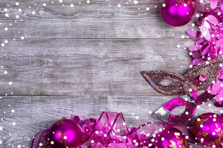 Christmas festive mockup. Xmas pink decorations. Creative frame of pink Christmas balls, tinsel, ribbon, carnival mask and snow on white wooden background. Top view, flat lay, copy space.