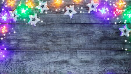 Christmas festive mockup. Xmas decorations. Creative border of white Christmas toys stars, multicolored garland with luminous stars and snow on white wooden background. Top view, flat lay, copy space.