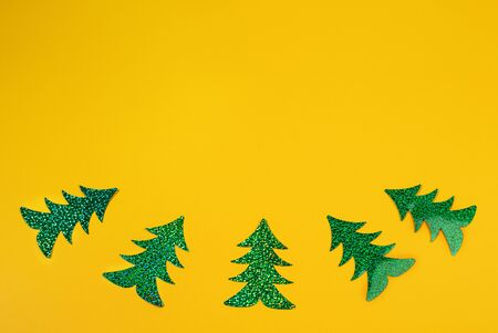Creative Christmas minimal mockup in trendy yellow with five bright green holographic Christmas trees laid out as curve. Top view, flat lay, copy space.