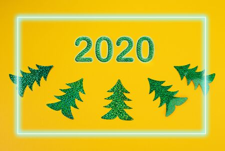 Creative Christmas mockup in trendy yellow with numbers 2020 and five bright green holographic Christmas trees laid out as curve and glowing neon frame overhand. Top view, flat lay.