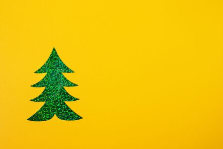 Creative Christmas minimal mockup in trendy yellow with one bright green holographic Christmas tree. Top view, copy space.