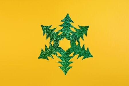 Creative Christmas minimal mockup in trendy yellow with snowflake of six bright green holographic Christmas trees. Top view, flat lay, copy space. Imagens