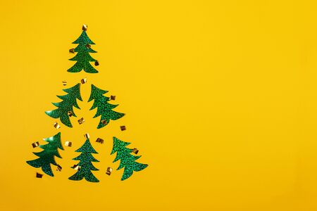 Creative Christmas minimal mockup in trendy yellow with Christmas tree of six bright green holographic Christmas trees. Top view, flat lay, copy space.