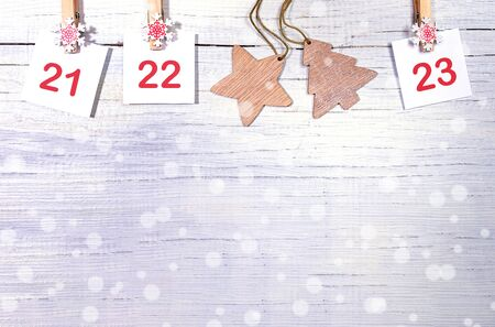 21-23 part of Advent calendar with numbers on white sheets on decorative clips and wooden christmas toys on white wooden snowy background with copy space. Xmas decorations. Stockfoto