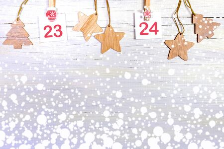 23-24 part of Advent calendar with numbers on white sheets on decorative clips and wooden christmas toys on white wooden snowy background with copy space. Christmas festive decorations. Stockfoto