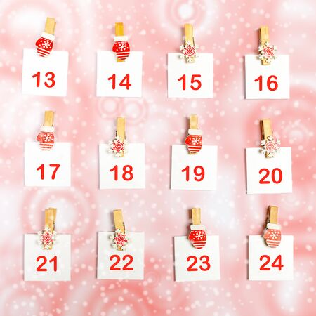 13-24 part of Advent calendar with numbers on white sheets on decorative clips on white-red snowy background. Xmas festive decorations.