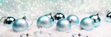 Merry Christmas or Happy new year wide banner with turquoise shiny and opaque christmas balls on snow on festive background with snow and bokeh. Imagens