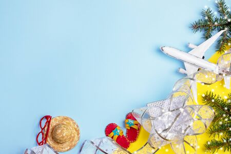 Christmas travel concept. Fir branches snow, festive ribbon, toy flops, hat, sunglasses and airplane on yellow-blue background. Top view, flat lay, copy space.