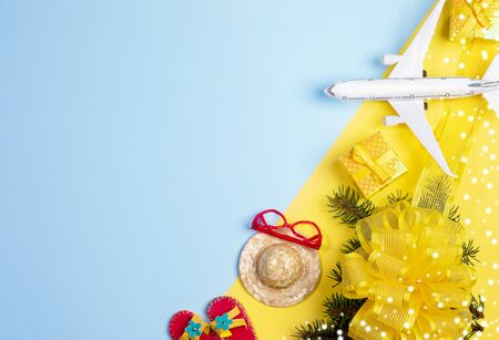 Christmas travel concept. Fir branches with bowknot and snow, gift boxes, toy flops, hat, sunglasses and airplane on yellow-blue background. Top view, flat lay, copy space. Stockfoto