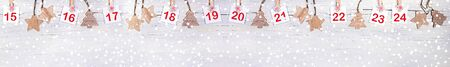 Christmas wide banner: 15-24 part of Advent calendar with numbers on white sheets on decorative clips and wooden christmas toys on white wooden snowy background. Copy space. Xmas festive decorations. Stockfoto