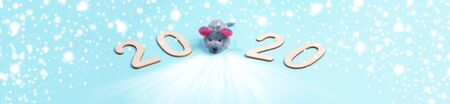 Creative banner of 2020 Merry Christmas or Happy new year. Wooden numbers with grey toy rat on light blue background with snow. Xmas decorations.