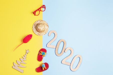 Flat lay of Merry Christmas and Happy new year 2020 travel concept. Creative Christmas tree of numbers and toy tree, rat, hat, Slippers, glasses on yellow-blue background. Top view, copy space. Stockfoto