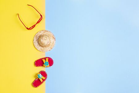 Merry Christmas or Happy new year or any holiday creative travel concept with toy hat, glasses and slippers on yellow-blue background. Top view, flat lay, copy space.