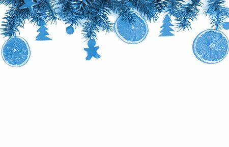Christmas handmade decorations in trendy color 2020 Classic Blue: border of  fir branches, dried oranges, cones, dried orange peel figurines: star, man, Christmas trees and balls on white. Top view, copy space.