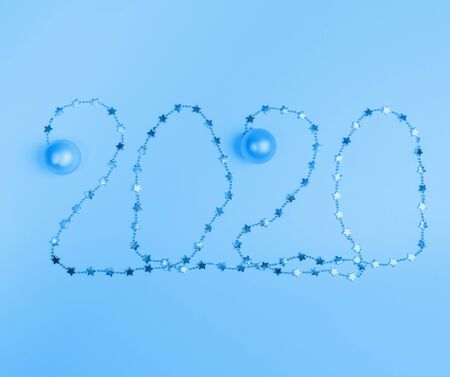 Christmas festive layout in trendy  Classic Blue color. Creative numbers 2020 of shiny Christmas garland with small stars and Christmas balls. Top view, flat lay.