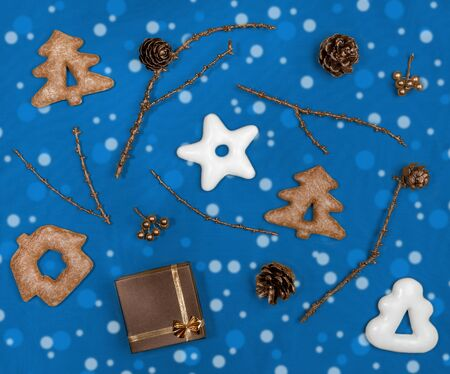 Christmas flat lay layout on trendy 2020 Classic Blue. Glazed gingerbread, bronze painted twigs, cones and gift box.