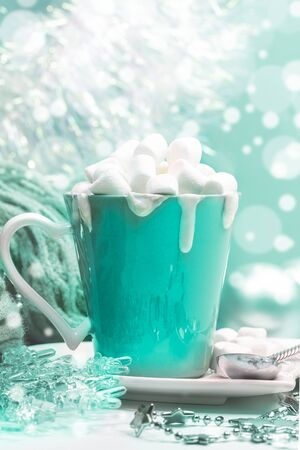 Cup of cocoa with cream with marshmallows, Christmas decor on background with bokeh in trendy color 2020 Aqua Menthe.