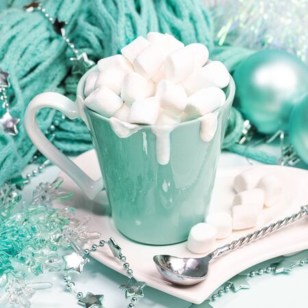 Xmas still life with cocoa or chocolate with cream and marshmallows, knitted scarf, Christmas decor in trendy color 2020 Aqua Menthe.