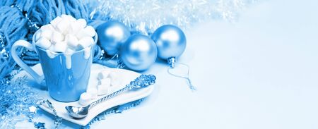 Christmas banner toned in 2020 Classic Blue. Cup of cocoa with cream and marshmallows, Christmas decorations.