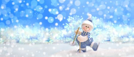 Christmas festive banner: toy felted snowman on skis on blue Christmas background with bokeh. Stockfoto