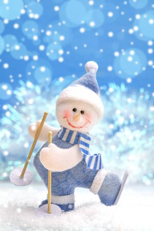 Toy felted snowman on skis on snow on blue Christmas background with bokeh.