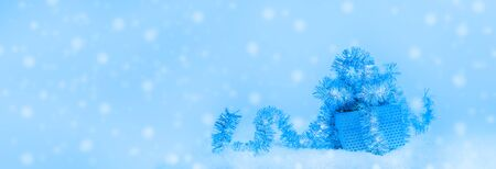 Festive Christmas banner in trendy color 2020 Classic Blue. Gift box decorated with shiny tinsel in snow on background with snow. Selective focus, copy space.
