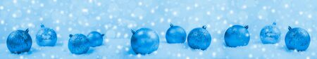 Festive wide Christmas banner in trendy color 2020 Classic Blue. Ornate shiny blue christmas balls in snow on background with snow and bokeh. Selective focus.