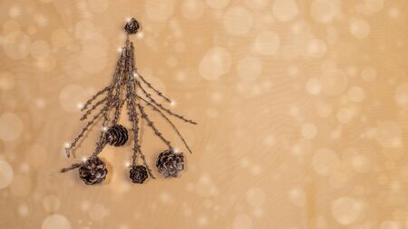 Creative Christmas mockup. Christmas tree of painted bronze twigs with cones on golden backdrop with bokeh. Copy space.