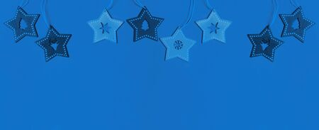 Christmas border in trendy Classic Blue. Hanging wooden stars with carved in them deer, Christmas tree, snowflake, star.