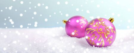 Christmas or New year festive banner with two pink christmas balls on snow on light background with snow. Close-up, copy space. Selective focus.