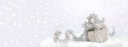 Festive Christmas banner. Silver gift box decorated with shiny tinsel in snow on light gray background with snow. Stockfoto