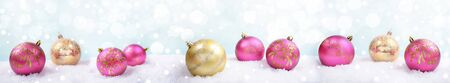 Festive Christmas banner with pink and golden christmas balls on light background with snow and bokeh. Selective focus.