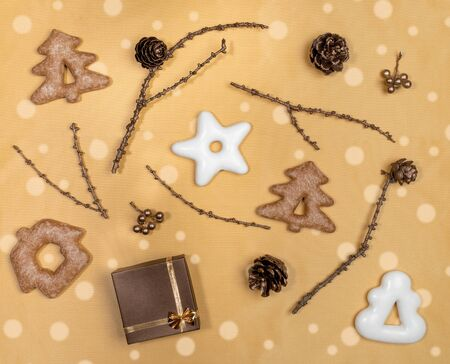 Christmas flat lay layout on golden background. Glazed gingerbread, bronze painted twigs with cones and gift box.