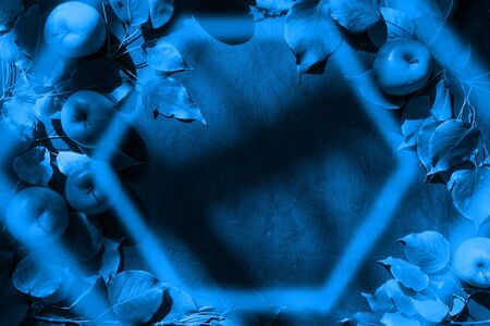 Trendy 2020 Classic Blue background with apples and leaves, hexagon frame and shadows above. Top view, flat lay, copy space. Blue toned image.