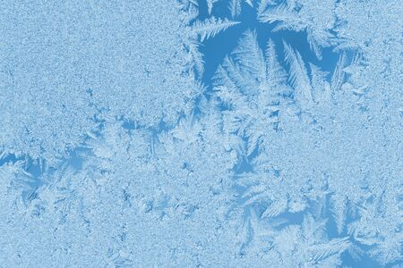 Christmas or New Year natural background in trendy color 2020 Classic Blue. Beautiful winter frosty pattern bizarre form on window glass. Blue toned image, copy space, horizontal orientation.