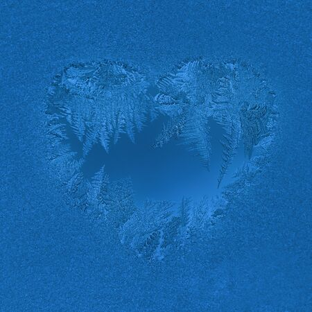 Christmas natural background in trendy color 2020 Classic Blue. Frosty window pattern in heart shape. Selective focus, square photo.