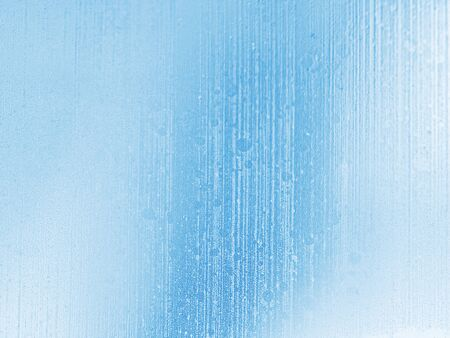 Winter blue and white blurred background of frozen streams of water on window glass. Blue toned natural abstract background. Stockfoto