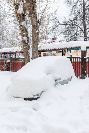 Entirely snowbound grey car is standing fixedly in snowdrift in yard house. Winter cityscape. Stockfoto