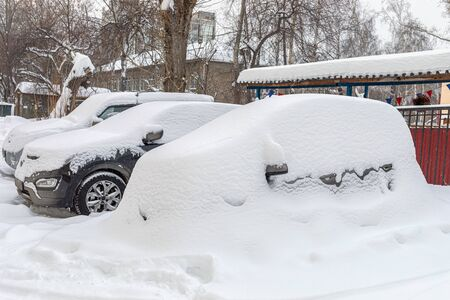 Heavily snowbound cars are standing fixedly in snow in yard house. Winter cityscape.